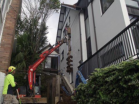 Cleaning auger after earth drilling in tight Remuera site between existing houses