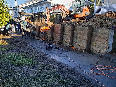 Concreting area in front of new timber retaining wall in Onehunga